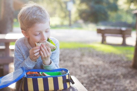 beautiful schoolboy eating sandwich for lunch during recess time at school